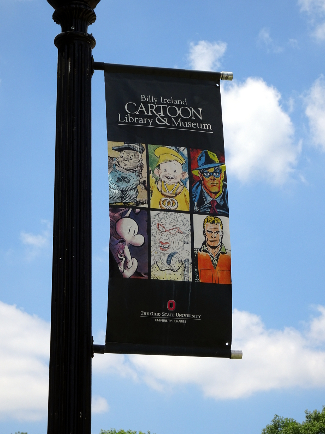 A banner outside the Billy Ireland Library & Museum. The image on the upper left is Billy Ireland's caricature of himself.